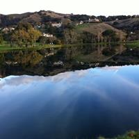 The lake provides a reflection of the beautiful surrounding of the golf course and hills. Blue skies are and warm days are abundant.  Corral de Tierra Country Club championship golf course on the Monterey Peninsula off Highway 68 between Monterey and Salinas.